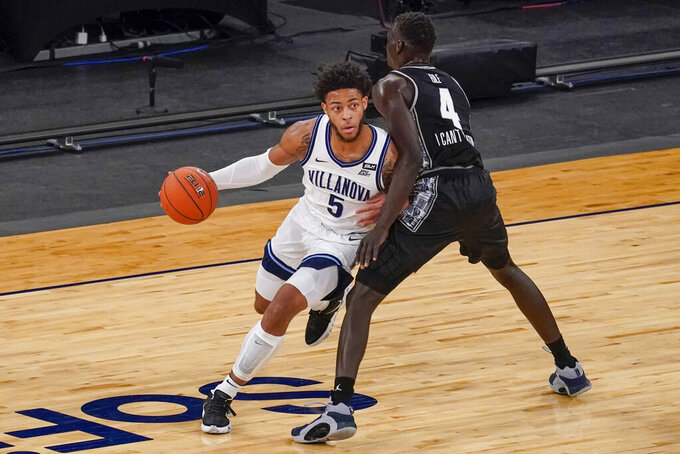 Villanova guard Justin Moore (5) drives against Georgetown forward Chudier Bile (4) during the first half of an NCAA college basketball game in the quarterfinals of the Big East conference tournament, Thursday, March 11, 2021, in New York. (AP Photo/Mary Altaffer)