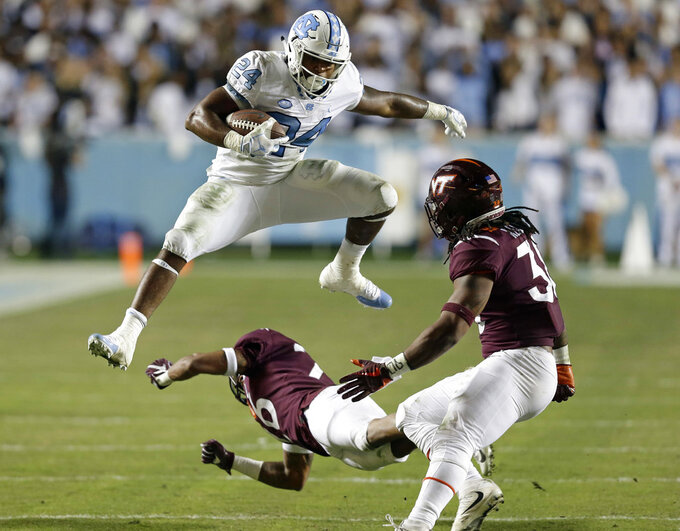 North Carolina's Antonio Williams (24) jumps over Virginia Tech's Jovonn Quillen as Virginia Tech's Rico Kearney looks for a tackle during the first half of an NCAA college football game in Chapel Hill, N.C., Saturday, Oct. 13, 2018. (AP Photo/Gerry Broome)