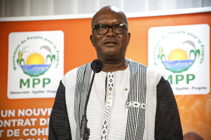President Roch Marc Christian Kabore addresses supporters in Ouagadougou after learning he will serve another five years as Burkina Faso's president, according to provisional results announced by the National Independent Electoral Commission Thursday Nov 26, 2020. (AP Photo/Sophie Garcia)