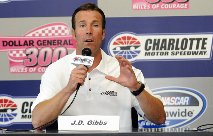 FILE - In this Oct. 14, 2011 file photo, J.D. Gibbs, president of Joe Gibbs Racing, speaks during a news conference before the NASCAR Nationwide auto race at Charlotte Motor Speedway in Concord, N.C.   Joe Gibbs Racing says co-founder J.D. Gibbs, the eldest son of team owner and Pro Football Hall of Fame coach Joe Gibbs, has died. He was 49. The team announced J.D. Gibbs' death on Saturday, Jan. 12, 2019,  saying he passed from complications following a long battle with a degenerative neurological disease. (AP Photo/Mike McCarn)