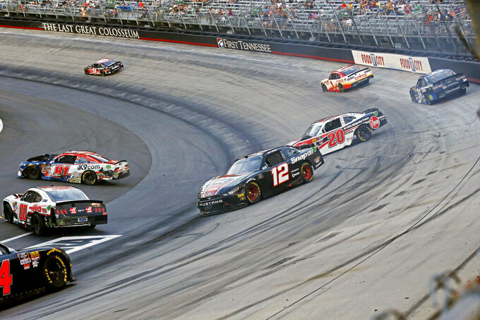The cars of Joey Logano (12), Christopher Bell (20), Cole Custer (00) and Erik Jones (81) sit on the track after wrecking as others pass during a NASCAR Xfinity Series auto race Friday, Aug. 16, 2019, in Bristol, Tenn. (AP Photo/Wade Payne)