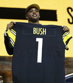 Michigan linebacker Devin Bush poses with his new jersey after the Pittsburgh Steelers selected Bush in the first round at the NFL football draft, Thursday, April 25, 2019, in Nashville, Tenn. (AP Photo/Mark Humphrey)
