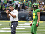 Oregon head coach Mario Cristobal, left, celebrates an extra point conversion with quarterback Justin Herbert, right, during the first half of an NCAA college football game against Nevada Saturday, Sept. 7, 2019, in Eugene, Ore. (AP Photo/Chris Pietsch)