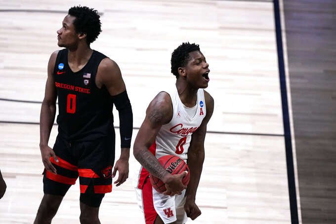 Houston guard Marcus Sasser, right, celebrates as Oregon State guard Gianni Hunt (0) looks on during the second half of an Elite 8 game in the NCAA men's college basketball tournament at Lucas Oil Stadium, Monday, March 29, 2021, in Indianapolis. Houston won 67-61. (AP Photo/Michael Conroy)