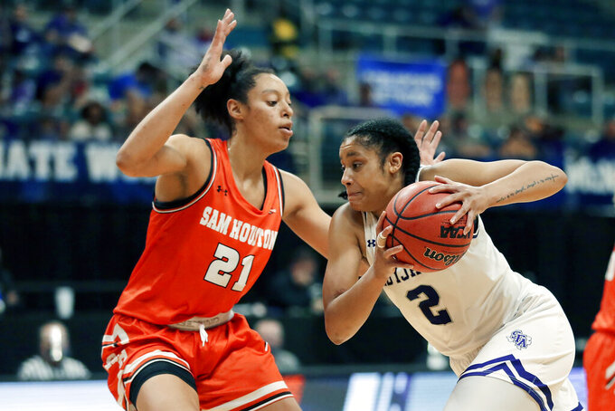 Stephen F. Austin guard Alyssa Mayfield (2) drives around Sam Houston State forward Madelyn Batista (21) during the first half of an NCAA college basketball game for the Southland Conference women's tournament championship Sunday, March 14, 2021, in Katy, Texas. (AP Photo/Michael Wyke)