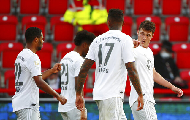 Benjamin Pavard of Munich, right, celebrates his side's second goal during the German Bundesliga soccer match between Union Berlin and Bayern Munich in Berlin, Germany, Sunday, May 17, 2020. The German Bundesliga becomes the world's first major soccer league to resume after a two-month suspension because of the coronavirus pandemic. (AP Photo/Hannibal Hanschke, Pool)