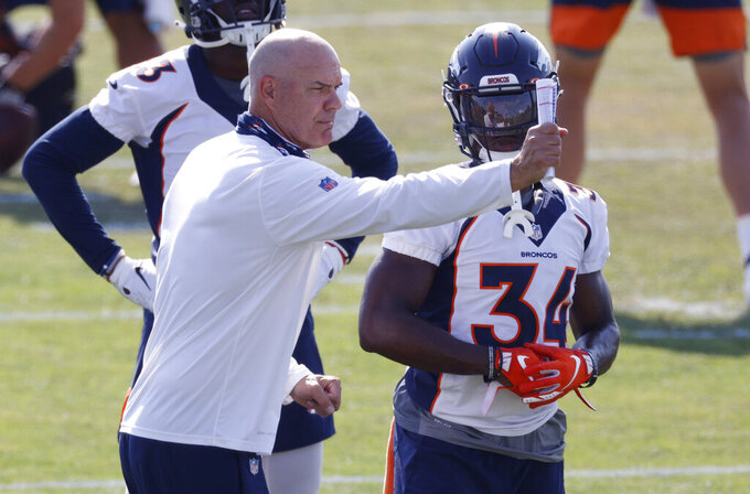 FILE - In this Aug. 19, 2020, file photo, Denver Broncos defensive coordinator Ed Donatell, left, directs cornerback Essang Bassey who takes part in drills during an NFL football practice at the team's headquarters in Englewood, Colo. Donatell made his first public comments on Thursday, Dec. 10, 2020, since testing positive for COVID-19 on Halloween. (AP Photo/David Zalubowski, File)