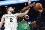 Boston Celtics' Jaylen Brown (7) and Brooklyn Nets' Joe Harris (12) reach for a rebound during the first half of an NBA basketball game in Boston, Wednesday, Nov. 27, 2019. (AP Photo/Michael Dwyer)