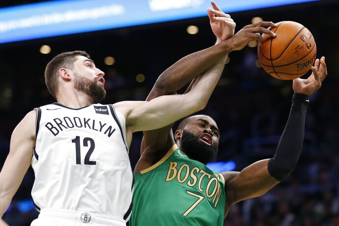 Boston Celtics' Jaylen Brown (7) and Brooklyn Nets' Joe Harris (12) reach for a rebound during the first half of an NBA basketball game in Boston, Wednesday, Nov. 27, 2019. (AP Photo/Michael Dwyer)