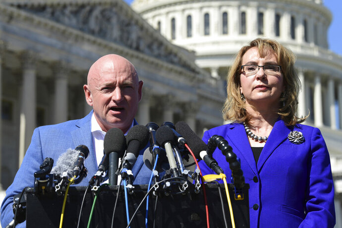 FILE- In this Oct. 2, 2017, file photo former Rep. Gabrielle Giffords, D-Ariz., right, listens as her husband Mark Kelly, left, speaks on Capitol Hill in Washington. Kelly said Tuesday, Feb. 12, 2019, that he's running to finish John McCain's term in the U.S. Senate. (AP Photo/Susan Walsh, File)