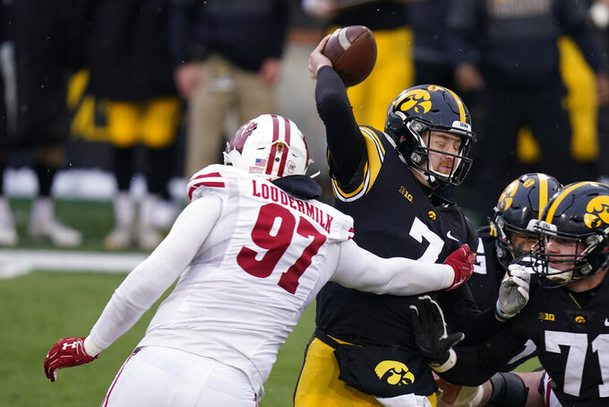Iowa quarterback Spencer Petras (7) is sacked by Wisconsin defensive end Isaiahh Loudermilk (97) during the first half of an NCAA college football game, Saturday, Dec. 12, 2020, in Iowa City, Iowa. (AP Photo/Charlie Neibergall)
