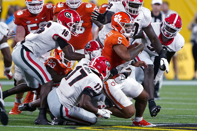 Clemson quarterback D.J. Uiagalelei is tackled by Georgia defenders during the second half of an NCAA college football game Saturday, Sept. 4, 2021, in Charlotte, N.C. (AP Photo/Chris Carlson)
