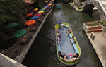 Using social distancing and other protective measures against COVID-19, visitors ride a river barges along the River Walk in San Antonio, Monday, June 15, 2020, in San Antonio. The barges, which have been closed due to the COVID-19 pandemic, began running again Monday. (AP Photo/Eric Gay)