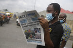 A man reads a newspaper reacting to the news of the assault on U.S Congress, on a street in Lagos, Nigeria, Thursday Jan. 7, 2021.  News reports show police with gun drawn as protesters try to break into the House Chamber at the U.S. Capitol on Wednesday, Jan. 6, in Washington, USA.(AP Photo/ Sunday Alamba)