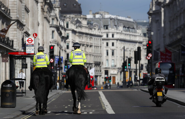 Mounted police officers patrol along a deserted Regent Street in London, as the country is in lockdown to help curb the spread of the coronavirus, Wednesday, April 15, 2020. Experts in the UK have warned that the economy could shrink by up to 35% as a knock on effect of the lockdown. The highly contagious COVID-19 coronavirus has impacted on nations around the globe, many imposing self isolation and exercising social distancing when people move from their homes. (AP Photo/Frank Augstein)