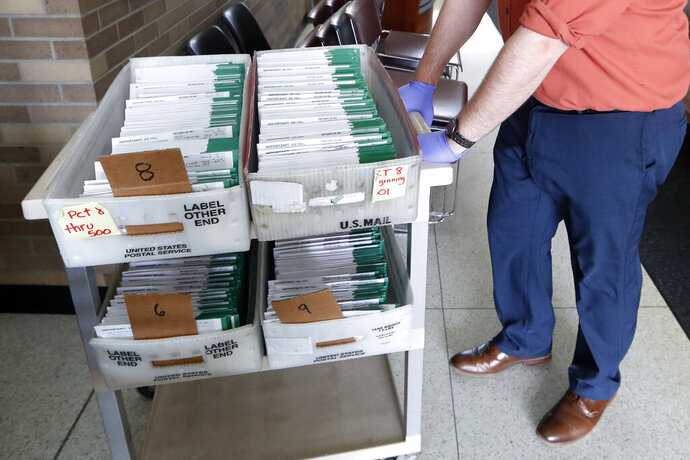 FILE - In this May 5, 2020, file photo, absentee ballots to be counted are moved at City Hall in Garden City, Mich. Data obtained by The Associated Press shows Postal Service districts across the nation are missing the agency's own standards for on-time delivery as millions of Americans prepare to vote by mail. (AP Photo/Paul Sancya, File)