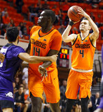 Oklahoma State's Thomas Dziagwa (4) shoots a three-point shot near Yor Anei (14) and TCU's Alex Robinson (25) in the first half of a NCAA college basketball game in Stillwater, Okla., Monday, Feb. 18, 2019. (Nate Billings/The Oklahoman via AP)
