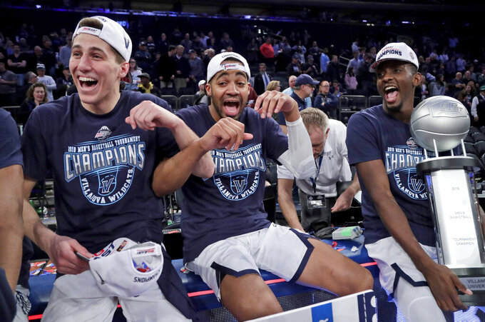 Villanova's Collin Gillespie, left, Phil Booth, and Dhamir Cosby-Roundtree celebrate after defeating Seton Hall 74-72 in an NCAA college basketball game in the championship of the Big East Conference tournament, Saturday, March 16, 2019, in New York. (AP Photo/Julio Cortez)