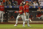 Philadelphia Phillies' Bryce Harper, center left, runs for home as he scores on an RBI-double by J.T. Realmuto during the first inning of a baseball game against the New York Mets, Sunday, Sept. 19, 2021, in New York. (AP Photo/Jason DeCrow)