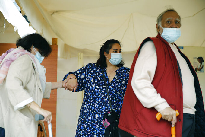 Puja Joshi, centre, who brought her parents, mother Sneh, left, and father Kamal, right, to receive a dose of the AstraZeneca COVID-19 vaccine manufactured by the Serum Institute of India and provided through the global COVAX initiative, at Kenyatta National Hospital in Nairobi, Thursday, April 8, 2021. (AP Photo/Brian Inganga)