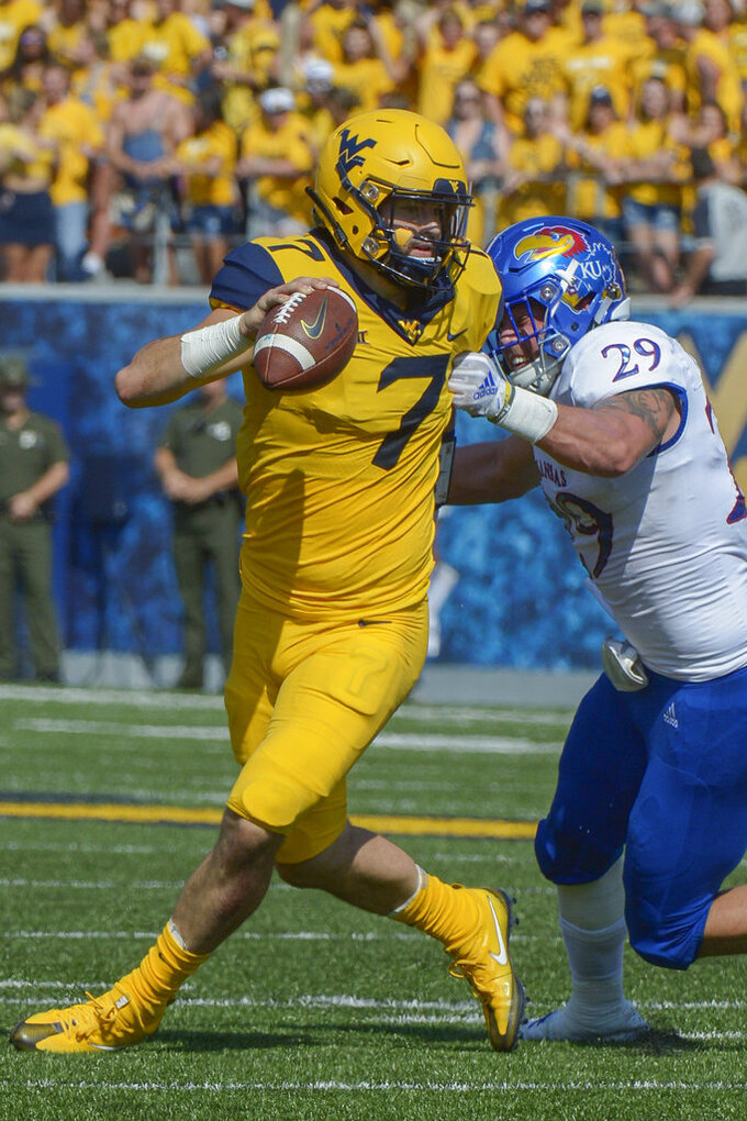 West Virginia quarterback Will Grier (7) is tackled by Kansas linebacker Joe Dineen Jr. (29) during the first half during the first half of an NCAA college football game in Morgantown, W. Va., Saturday Oct. 6, 2018. (AP Photo/Craig Hudson)