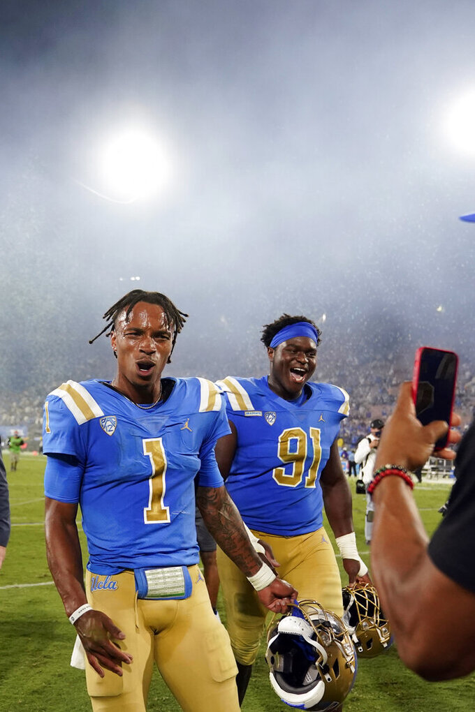UCLA quarterback Dorian Thompson-Robinson (1) and defensive lineman Otito Ogbonnia (91) walk off the field after the team's win over LSU during an NCAA college football game Saturday, Sept. 4, 2021, in Pasadena, Calif. (AP Photo/Marcio Jose Sanchez)