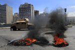 A Lebanese army humvee passes next of burned tires that set on fire by protesters to block a main highway, during a protest against the increase in prices of consumer goods and the crash of the local currency, in Beirut, Lebanon, Thursday, June 17, 2021. Shops, government offices, businesses and banks shut their doors Thursday in response to a call for a general strike by Lebanon's main labor union. (AP Photo/Hussein Malla)