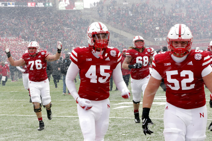 In this Nov. 17, 2018 photo, Nebraska players celebrate a 9-6 win over Michigan State in an NCAA college football game in Lincoln, Neb. Scott Frost's first Nebraska team is in position to finish with one more win than the Mike Riley-led Cornhuskers had a year ago. That would be no small accomplishment for the Huskers, who were the last power-five conference team to win this season following a program-worst 0-6 start. (AP Photo/Nati Harnik)
