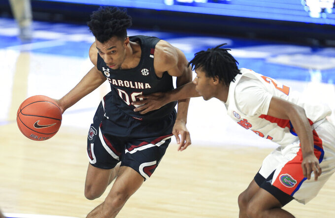 South Carolina guard AJ Lawson (00) dribbles around Florida guard Tyree Appleby (22) during the second half of an NCAA college basketball game Wednesday, Feb. 3, 2021, in Gainesville, Fla. (AP Photo/Matt Stamey)