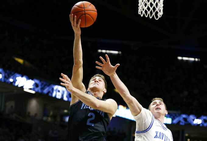 Villanova guard Collin Gillespie (2) puts up a shot in front of Xavier forward Jason Carter, right, during the second half of an NCAA college basketball game, Saturday, Feb. 22, 2020, in Cincinnati. (AP Photo/Gary Landers)