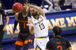 Notre Dame's Nikola Djogo (13) passes the ball between Miami's Anthony Walker (1) and Isaiah Wong (2) during the second half of an NCAA college basketball game Sunday, Feb. 14, 2021, in South Bend, Ind. Notre Dame won 71-61. (AP Photo/Robert Franklin)