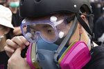 """In this Aug. 16, 2019, photo, Wayne, a 33-year-old self-described """"front line"""" protester, adjusts his gas mask stands along with other demonstrators in Tai Po, on Hong Kong's outskirts. Hong Kong's protest movement has reached a moment of reckoning after protesters occupying the airport held two mainland Chinese men captive, and pro-democracy lawmakers and fellow demonstrators question whether the whole operation has gone too far. (AP Photo/Vincent Thian)"""