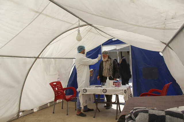 This photo provided on April 12, 2020, by the Syrian American Medical Society, which has been authenticated based on its contents and other AP reporting, shows a nurse checking a man for fever and other symptoms as part of the effort to contain and trace the coronavirus, in a tent outside Idlib Central Hospital, Idlib, northern Syria. Nine years of war have broken Syria into three rival parts, and each is struggling to cope with a common enemy that knows no conflict lines. Unable to work together, their divisions are hurting frantic efforts to mobilize against the coronavirus in a country where the health sector is already devastated by war. (Syrian American Medical Society via AP)