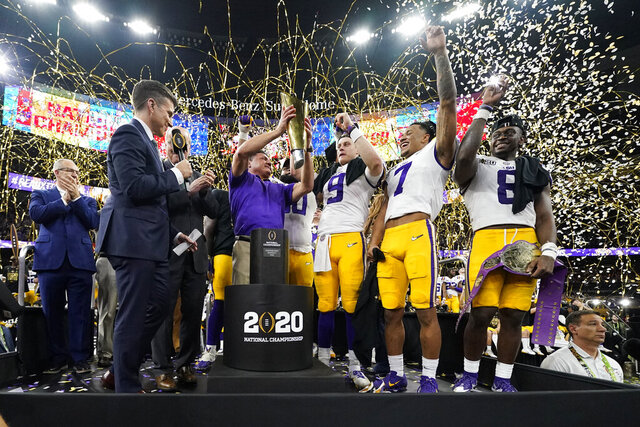 FILE - In this Jan. 13, 2020, file photo, LSU head coach Ed Orgeron holds the trophy after the team's victory over Clemson in an NCAA College Football Playoff national championship game in New Orleans. LSU has begun asking a number of football players to self-quarantine in the past week because of instances in which some players tested positive for COVID-19 after social interactions outside of the Tigers' training facility. (AP Photo/David J. Phillip, File)
