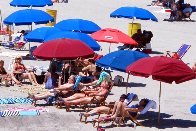 In this July 9, 2018 photo, beach-goers huddle under beach umbrellas on the sand in Atlantic City, N.J. The New Jersey Legislature is considering a bill in February 2020 to require beach umbrellas to be tethered to the sand to prevent injuries from flying umbrellas. (AP Photo/Wayne Parry)