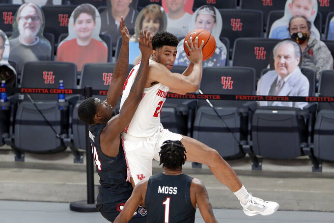 Houston guard Quentin Grimes, middle, jumps to pass the ball under pressure from South Carolina forward Keyshawn Bryant, left, and guard T.J. Moss (1) during the second half of an NCAA college basketball game Saturday, Dec. 5, 2020, in Houston. (AP Photo/Michael Wyke)