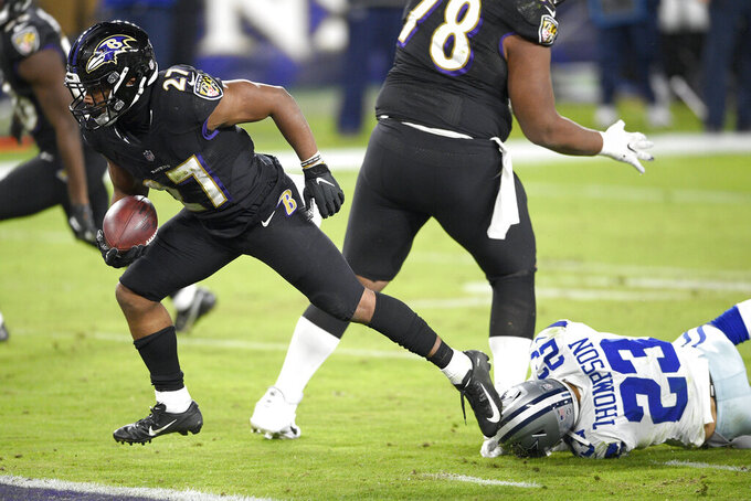 Baltimore Ravens running back J.K. Dobbins, left, gets by the tackle attempt of Dallas Cowboys strong safety Darian Thompson while scoring a touchdown during the second half of an NFL football game, Tuesday, Dec. 8, 2020, in Baltimore. (AP Photo/Nick Wass)