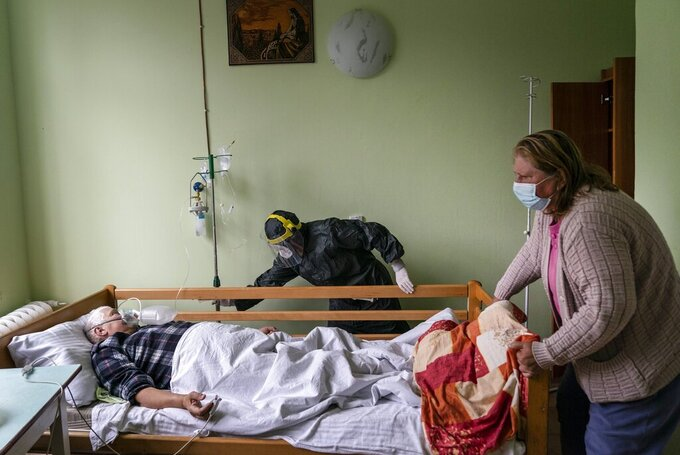 A nurse, center, moves a bed with a coronavirus patient in a hospital intensive care unit in Stryi, western Ukraine, on Tuesday, Sept. 29, 2020. Coronavirus infections in Ukraine began surging in late summer, and the ripples are hitting towns in the western part of the country. The government wants to avoid imposing a new lockdown, but officials acknowledge that the rising infections could make it necessary. (AP Photo/Evgeniy Maloletka)