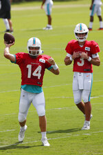 Miami Dolphins quarterback Ryan Fitzpatrick (14) runs a drill as quarterback Josh Rosen (3) looks on during practice at the NFL football team's training camp, Monday, Aug. 19, 2019, in Davie, Fla. Fitzpatrick is expected to start the Miami Dolphins' exhibition game this week, which suggests he's still the front-runner in his battle with Rosen for the starting job. (AP Photo/Wilfredo Lee)