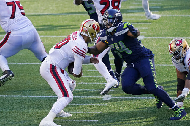 Seattle Seahawks middle linebacker Bobby Wagner, right, sacks San Francisco 49ers quarterback Jimmy Garoppolo during the first half of an NFL football game, Sunday, Nov. 1, 2020, in Seattle. (AP Photo/Elaine Thompson)