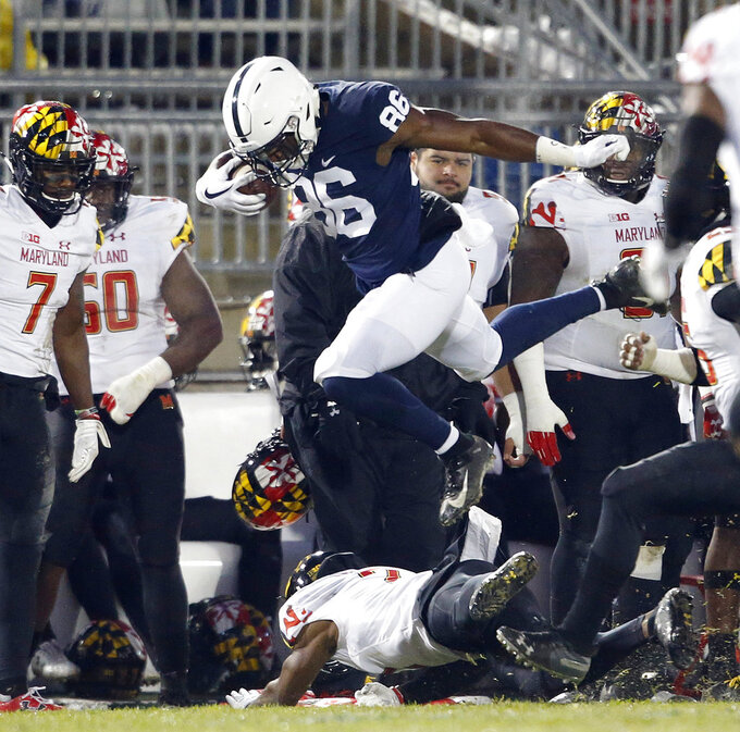 Penn State's Daniel George (86) leaps over Maryland's RaVon Davis (2) after a catch during the first half of an NCAA college football game in State College, Pa., Saturday, Nov. 24, 2018. (AP Photo/Chris Knight)
