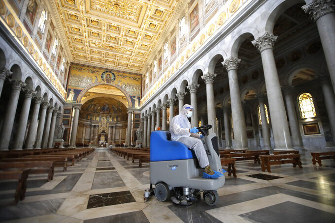 Church personnel sanitize St. Paul Outside the Walls Basilica to prevent the spread of COVID-19, in Rome, Saturday, May 16, 2020. Italy partially lifted lockdown restrictions last week after a two-month lockdown and from May 18 churches are expected to reopen to the public for masses. (AP Photo/Alessandra Tarantino)