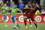 Seattle Sounders forward Nicolas Lodeiro, left, is challenged by Real Salt Lake midfielder Kyle Beckerman (5) during the first half of an MLS Western Conference semifinal playoff soccer match Wednesday, Oct. 23, 2019, in Seattle. (AP Photo/Ted S. Warren)