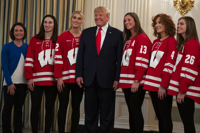 President Donald Trump poses for photos with members of the University of Wisconsin-Madison Women's Hockey Team during the NCAA Collegiate National Champions Day at the White House, Friday, Nov. 22, 2019, in Washington. (AP Photo/ Evan Vucci)