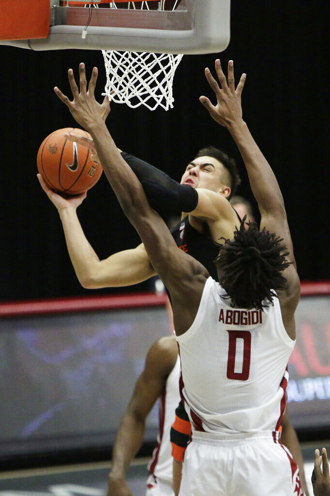 Oregon State guard Jarod Lucas, rear, shoots next to Washington State center Efe Abogidi during the second half of an NCAA college basketball game in Pullman, Wash., Wednesday, Dec. 2, 2020. Washington State won 59-55. (AP Photo/Young Kwak)