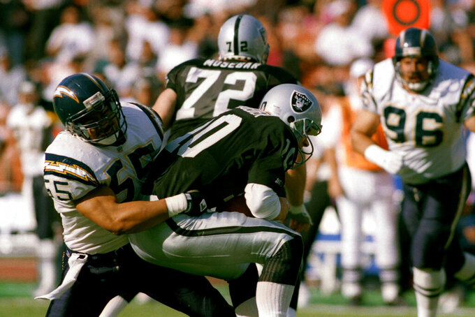 FILE - In this Dec. 20, 1992, file photo, Los Angeles Raiders quarterback Jay Schroeder is sacked for a 5-yard loss by San Diego Charger inside linebacker Junior Seau (55) during the second quarter of an NFL football game in Los Angeles. San Diego went for the hometown pick in 1990, selecting Oceanside native and Southern California standout Seau fifth overall. He ended up becoming one of the most popular players in franchise history with 12 consecutive Pro Bowl appearances. (AP Photo/Mark Terrill, File)