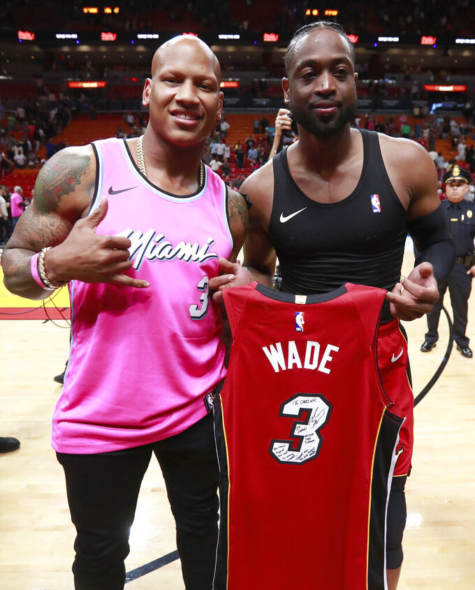 Miami Heat guard Dwyane Wade, right, poses with Pittsburgh Steelers linebacker Ryan Shazier after an NBA basketball game Friday, March 15, 2019, in Miami. Wade gave his game jersey to Shazier. The Milwaukee Bucks defeated the Heat 113-98. (AP Photo/Wilfredo Lee)