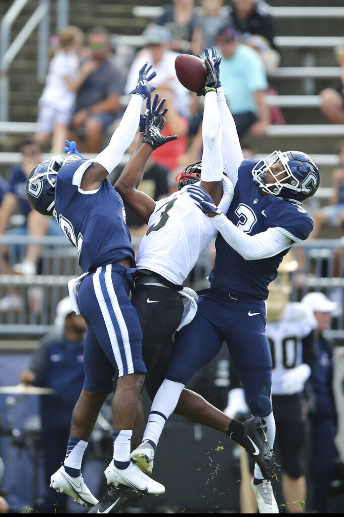 Connecticut defensive back Myles Bell (2) and defensive back Diamond Harrell (3) prevent Purdue wide receiver David Bell (3) from catching a pass during the first half of an NCAA football game on Saturday, Sept. 11, 2021, in East Hartford, Conn. (AP Photo/Stew Milne)