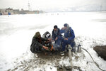 People sit around a fire to warm themselves after a heavy snowfall in Kabul, Afghanistan, Tuesday, Jan. 14, 2020. Severe winter weather has struck parts of Afghanistan and Pakistan, with heavy snowfall, rains and flash floods that left dozens dead, officials said Monday as authorities struggled to clear and reopen highways and evacuate people to safer places. (AP Photo/Rahmat Gul)