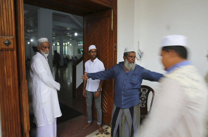 A Sri Lankan Muslim guides people for Friday prayers inside a mosque, in Colombo, Sri Lanka, Friday, April 26, 2019. Across Colombo, there was a visible increase of security as authorities warned of another attack and pursued suspects that could have access to explosives. Authorities had told Muslims to pray at home rather than attend communal Friday prayers that are the most important religious service for the faithful. At one mosque in Colombo where prayers were still held, police armed with Kalashnikov assault rifles stood guard outside. (AP Photo/Manish Swarup)